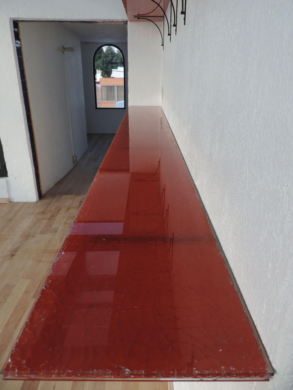 Las repisas son vidrio craquelado color rojo y en el piso se coloco duela de madera natural