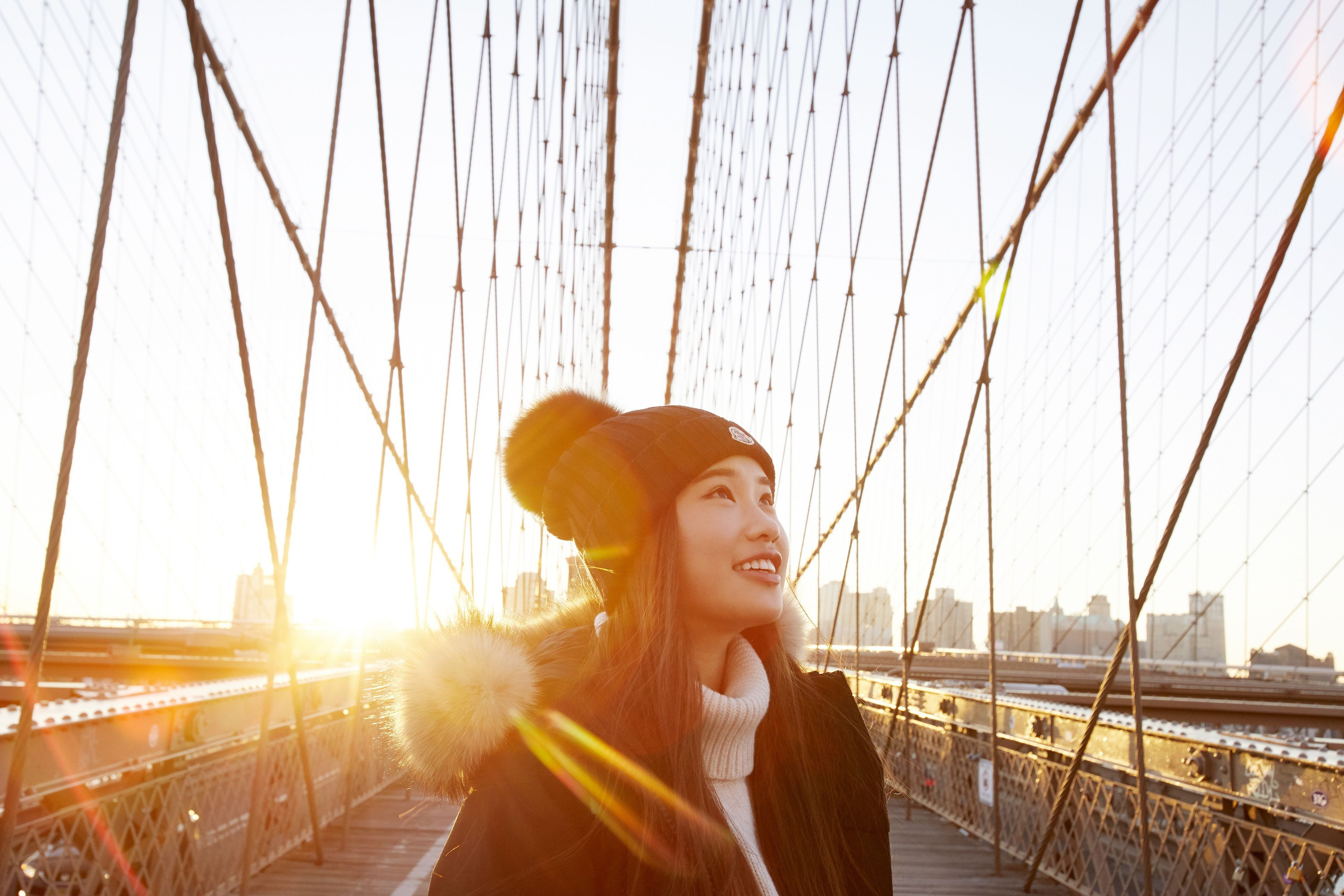 woman in winter clothing smiling and looking up with sun in background on brooklyn bridge 5b082fd