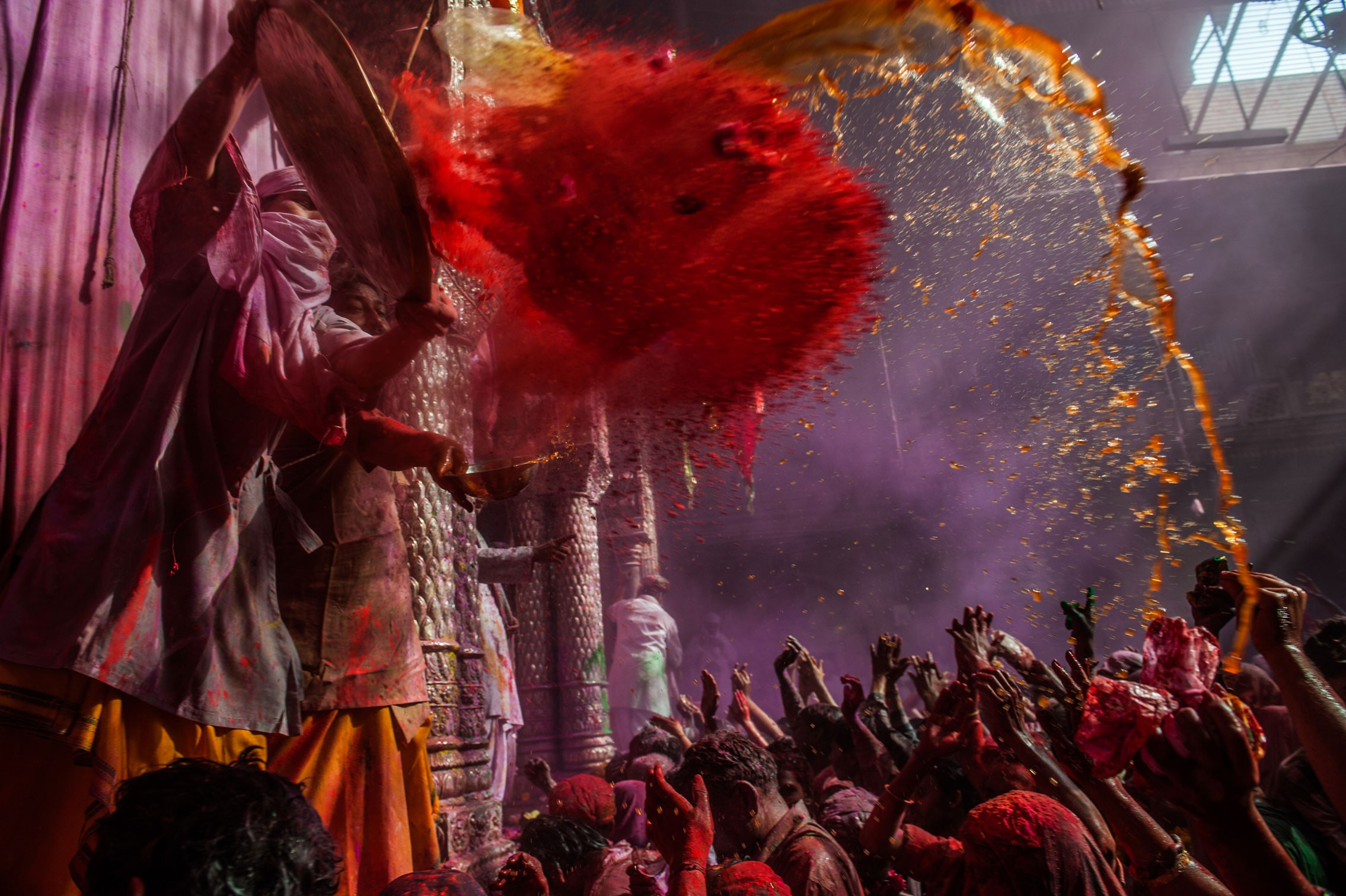 A Hindu priest throws coloured powder at devotees during Holi festival at the Banke Bihari