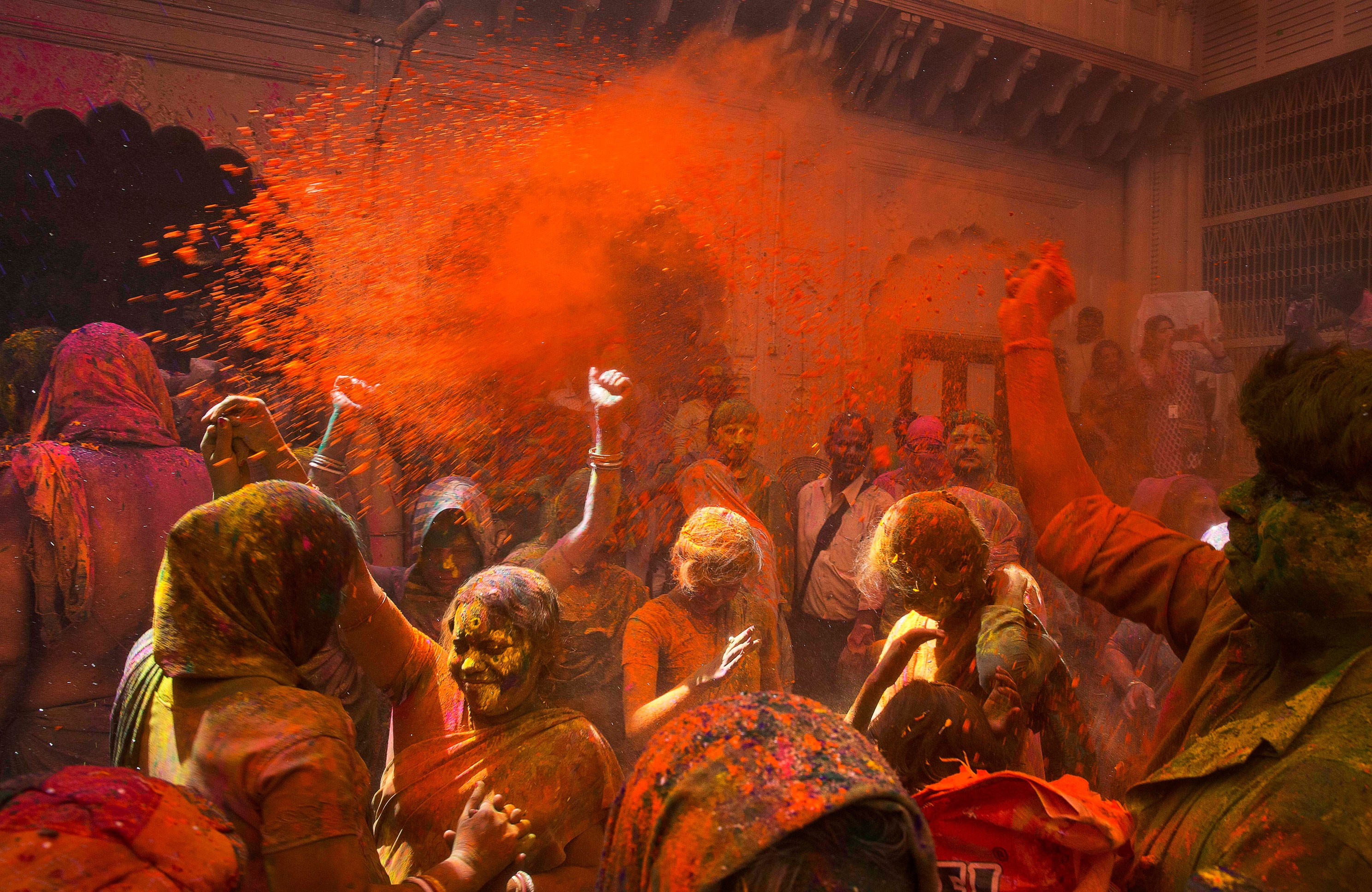 Locals and Indian Hindu widows throw flower petals and colored powder during Holi celebrations at the